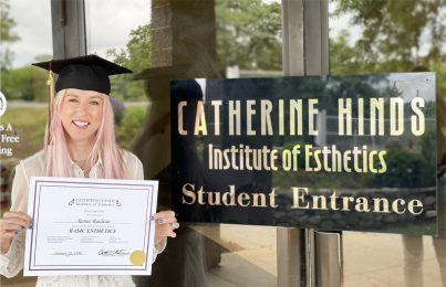 Renée Rouleau in front of Catherine Hinds School with diploma