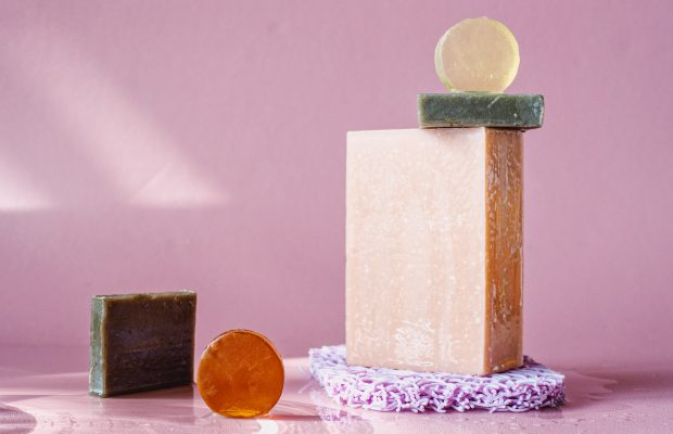 Bars of facial soap stacked on pink background