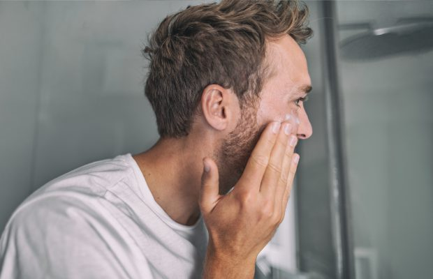 Man applying skincare products on face