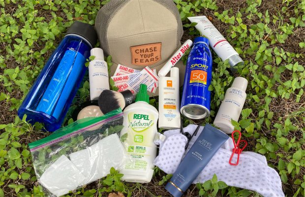 Items for camping skincare routine laid out on grass