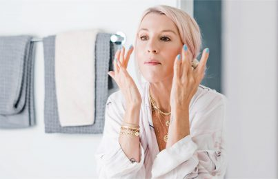 Renée Rouleau washing her face while looking in mirror